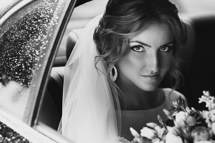 Beautiful blonde bride posing in wedding car on rainy day b&w ** Note: Visible grain at 100%, best at smaller sizes