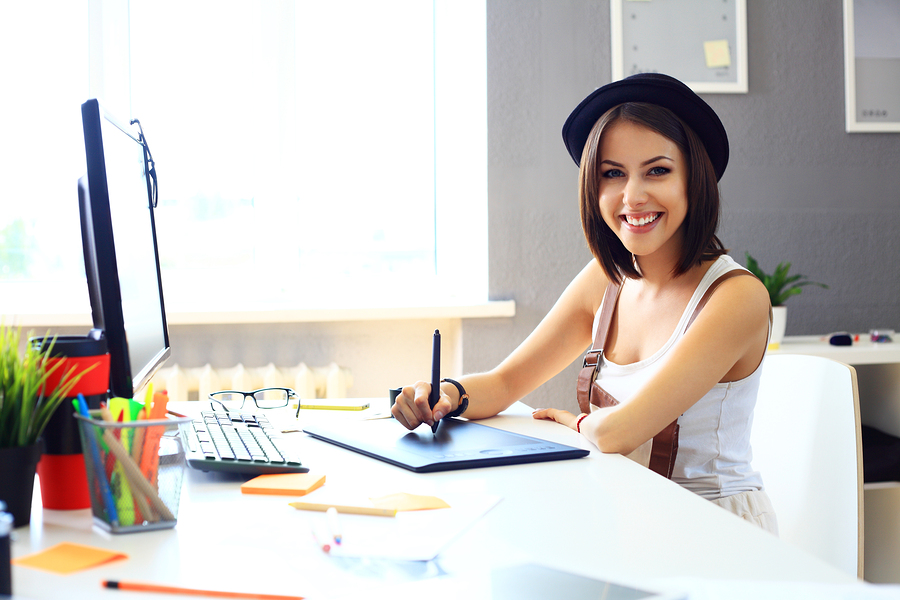 Young Female Designer Using Graphics Tablet While Working With C